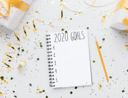 Notebook with 2020 goals and gift boxes on white background, copy space