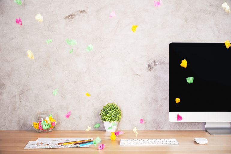 black computer screen with colorful paper balls floating in the air