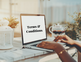 laptop on desk, screen says terms and conditions