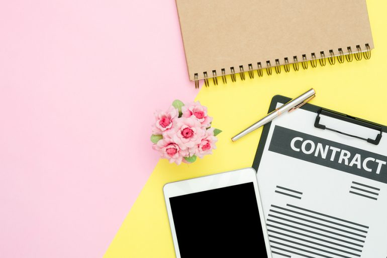 pink and yellow background with a notebook, tablet and business contract on top
