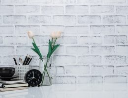 desk with flowers, pile of books, black coffee mug and black clock against a gray brick wall